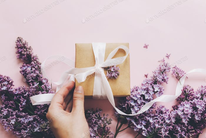 Hand holding gift box with ribbon and lilac flowers on pink background