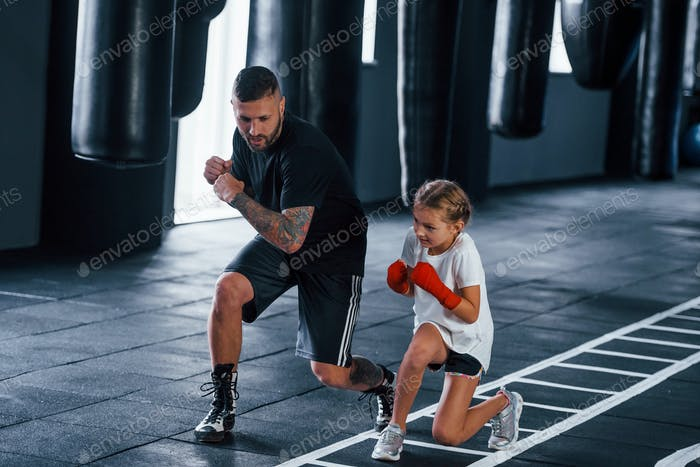 Basic punches. Young tattooed boxing coach teaches cute little girl in the gym