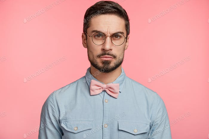 Serious strict male boss has trendy hairdo, wears formal shirt with bow tie, listens seriously semin