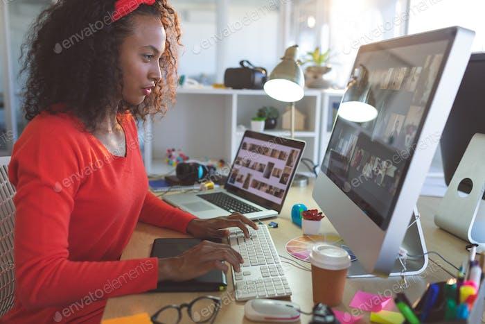 Female graphic designer working on desktop pc at desk in a modern office