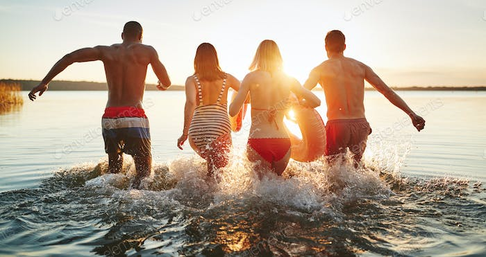 Diverse young friends splashing into a lake together at sunset