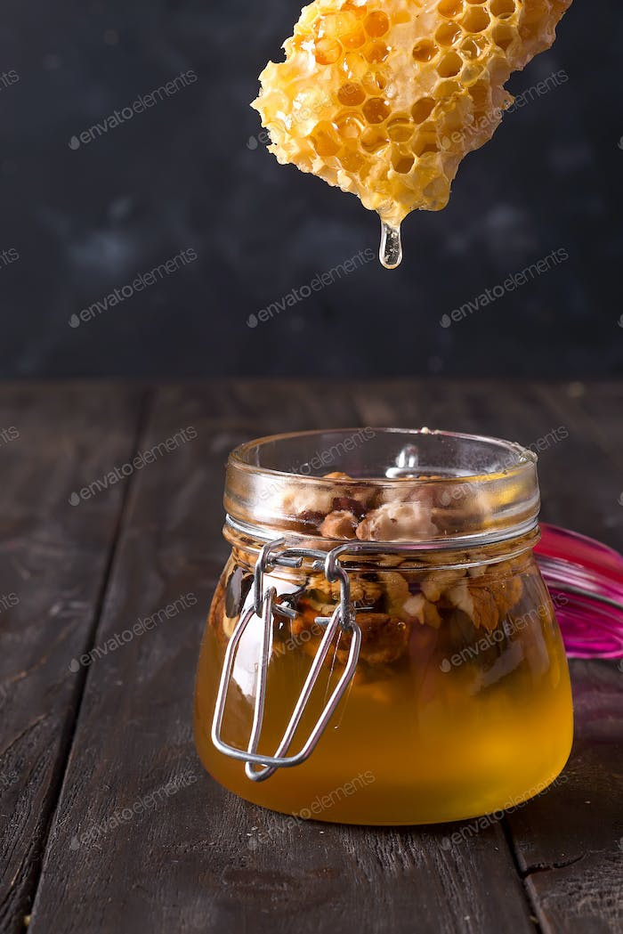honey comb dripping from dipper into jar with nuts on old wooden table. Healthy eat
