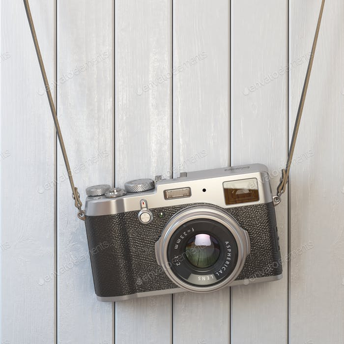 Vintage retro photo camera hanging on the white wooden wall.