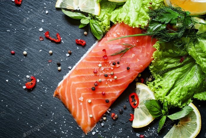 Tasty piece of salmon fillet with herbs, spices, lemon, salt, pepper