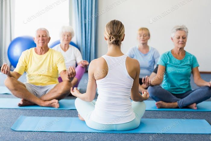 Инструктор, занимающий йогу с пожилыми людьми