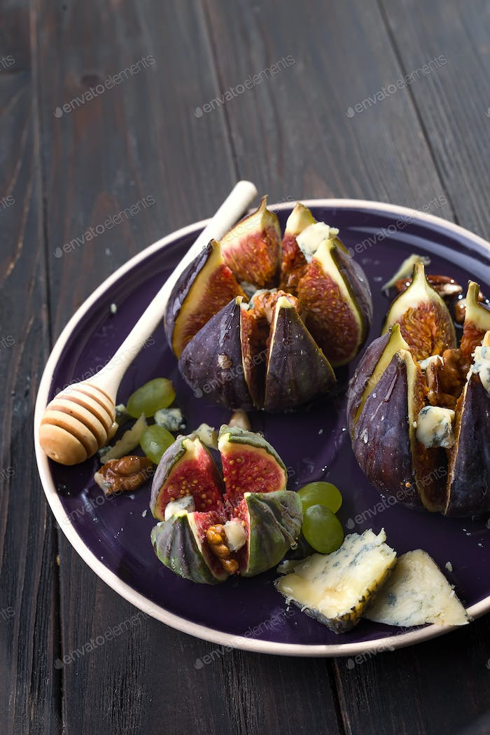 baked figs with goat cheese,walnuts and honey on ceramic plate