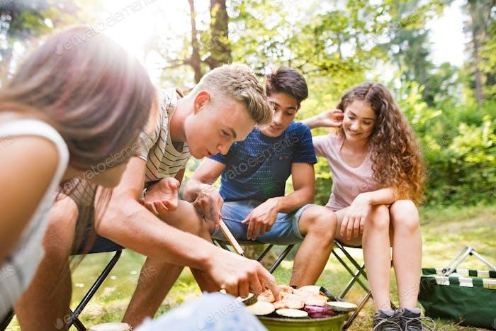 Jugendliche Camping, Kochen Gemüse auf dem Grill.