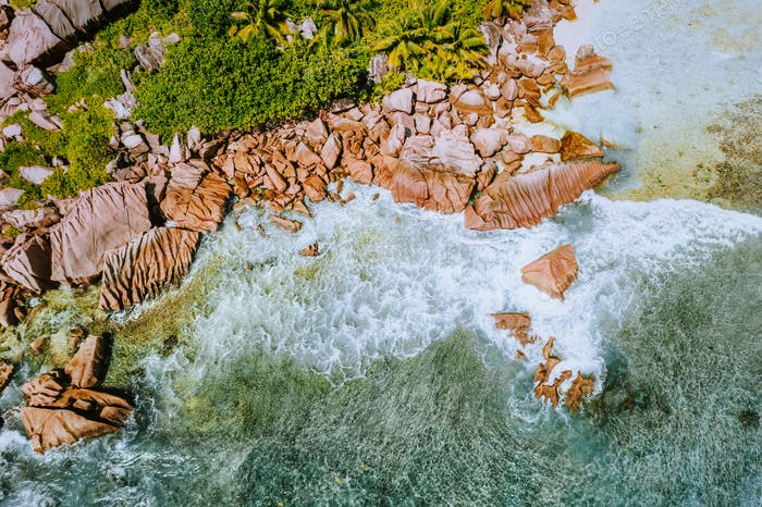 Seychelles La Digue Island. Aerial top view of ocean waves and huge bizarre granite rocks on the