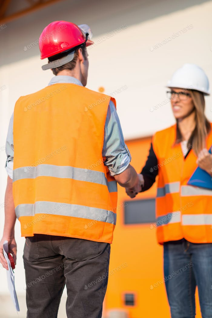 Business handshake on construction site