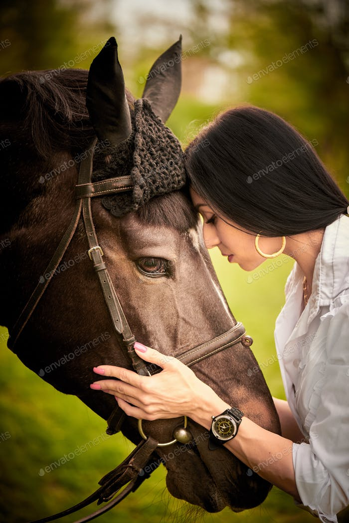 A young woman hugs a horse