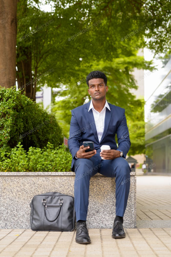 Portrait of African businessman using phone and holding take away coffee cup outdoors in city while