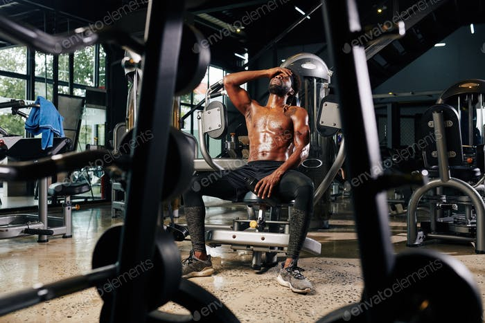 Tired shirtless sportsman resting in gym machine