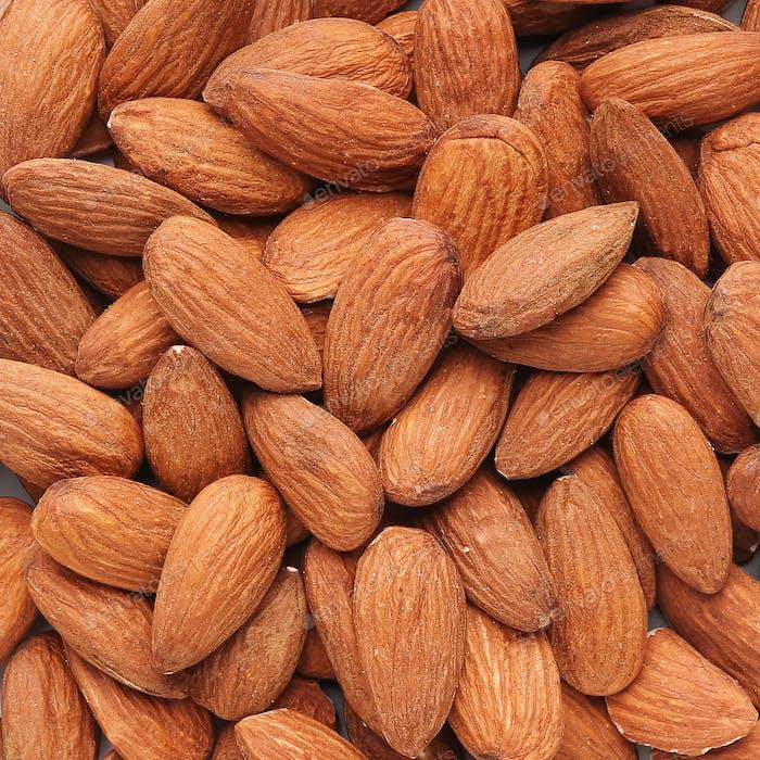 Heap of fresh almonds background texture closeup