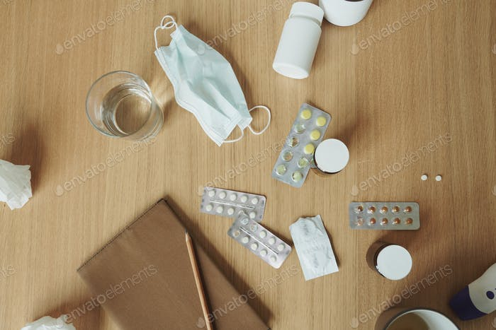 Wooden table with notebook, medical mask, tablets and pills, glass of water