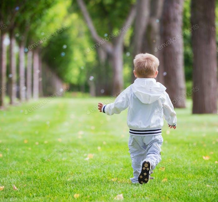 Little boy running in park, rear view