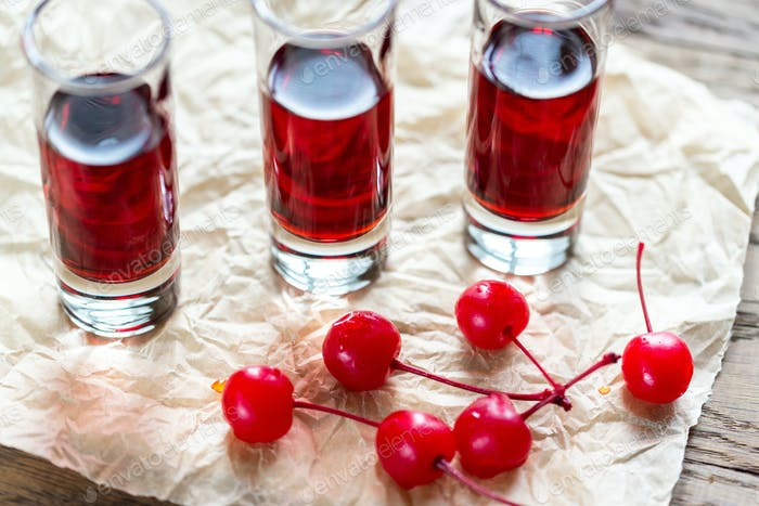 Glasses of cherry brandy with cocktail cherries