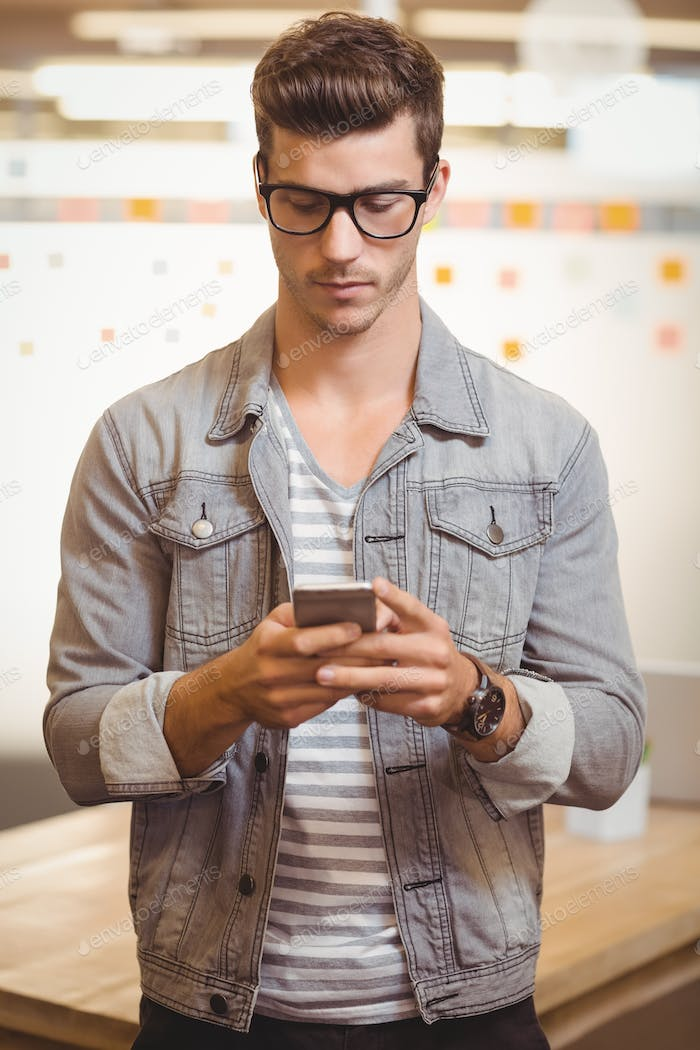 Businessman texting on phone in office