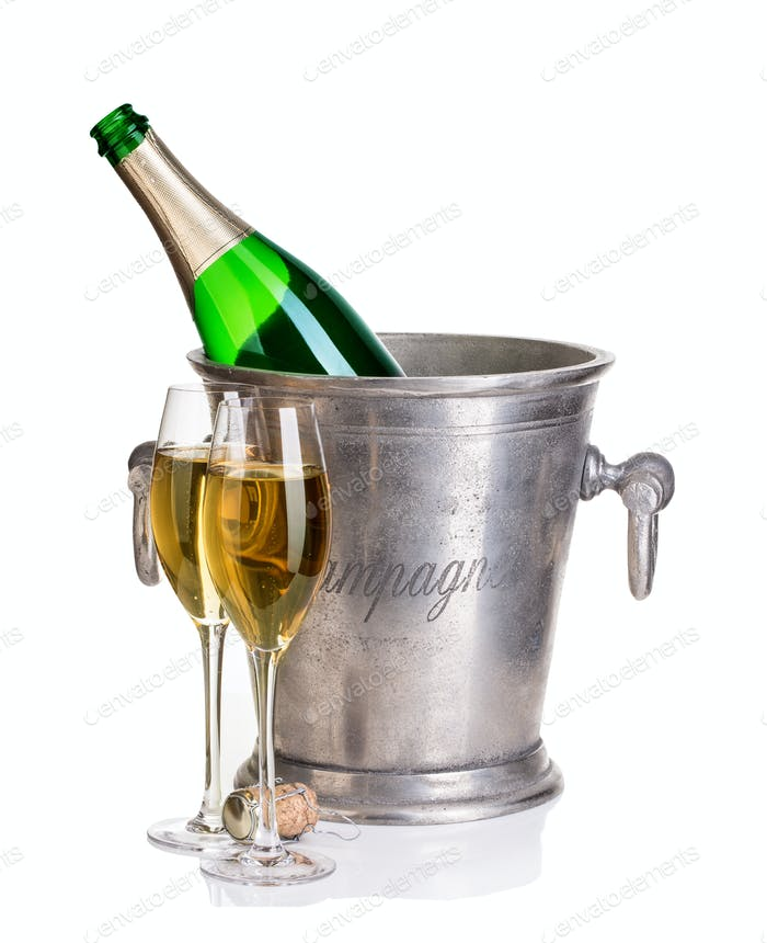 Champagne bottle in ice bucket with glasses of champagne.