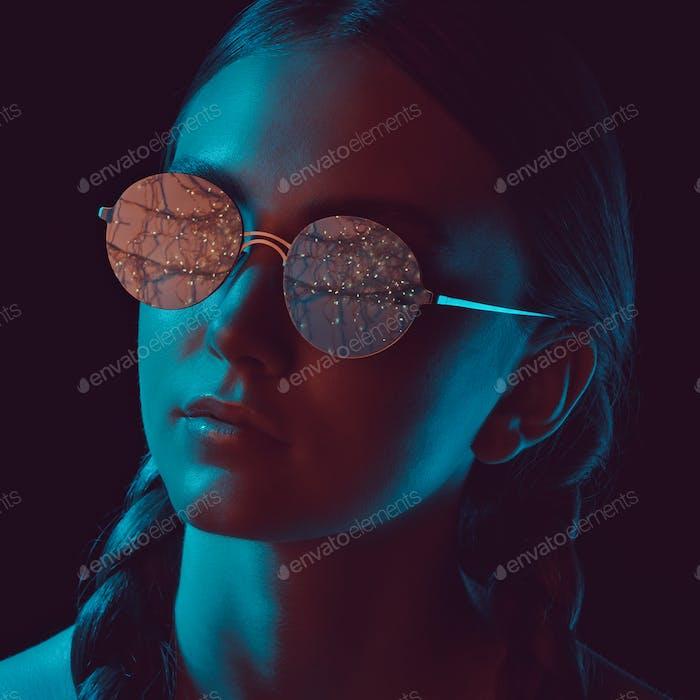 headshot of thoughtful young woman in stylish round sunglasses