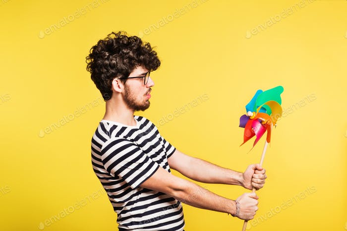 Studio portrait of a young man holding a windmill on a yellow background.