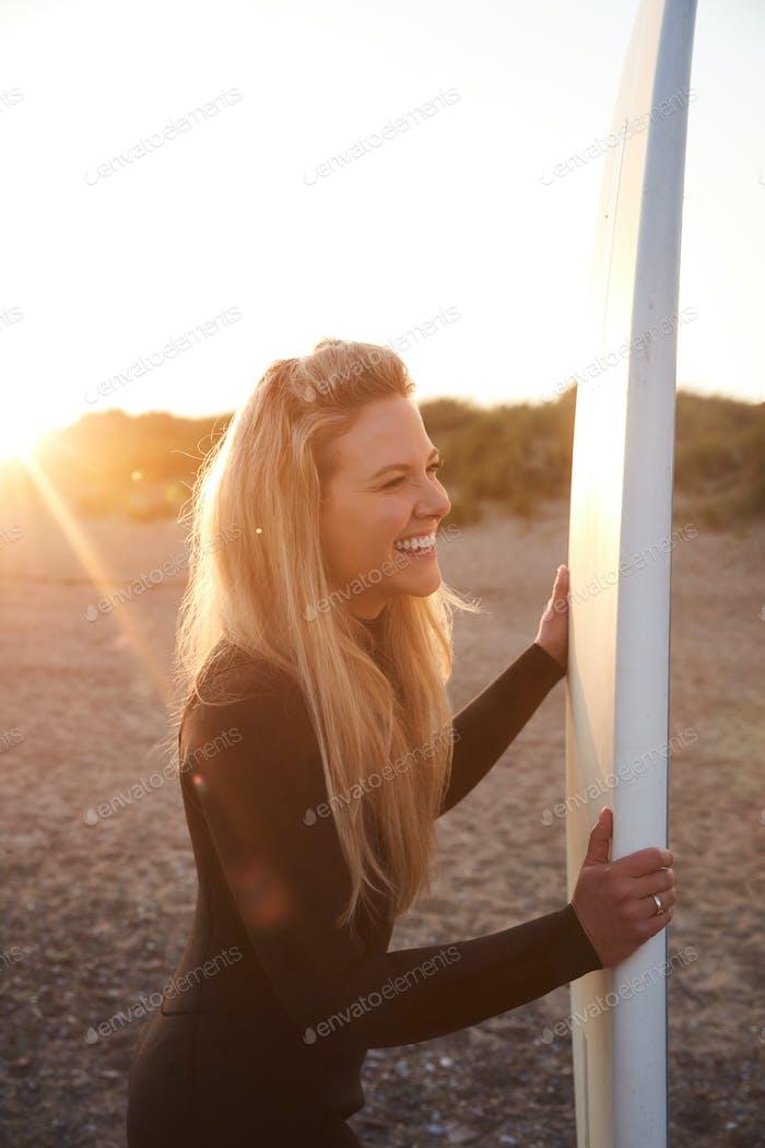 Frau Tragen Neoprenanzug Halten Surfbrett genießen Surfen Aufenthalt am Strand als Sonne Sets