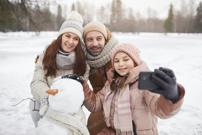 Happy Family Taking Photo with Snowman