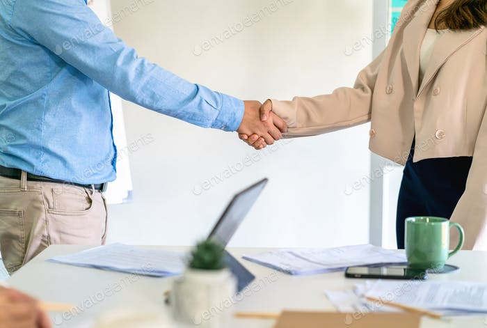Closeup handshake of asian partner businessman and businesswoman in modern office after deal
