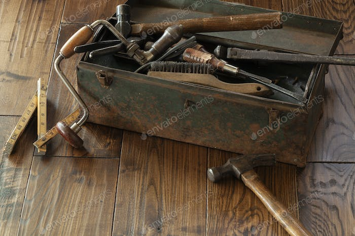 Antique tools and grungy toolbox on rough dark wood surface