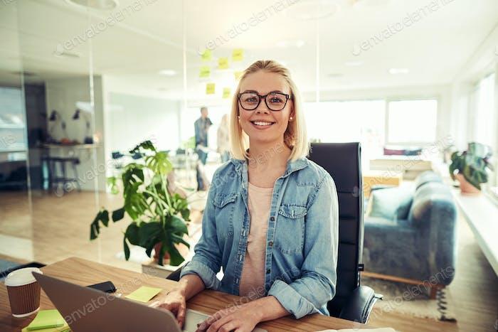 Улыбаясь бизнесвумен сидит за ее стол в офисный стол