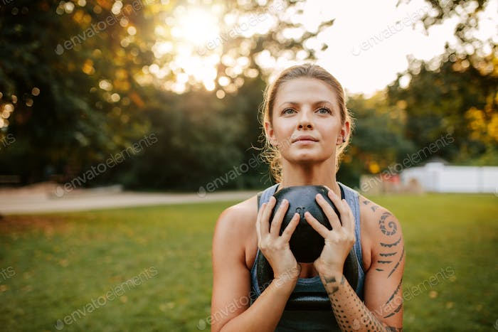 Fit young woman doing workout with kettlebell