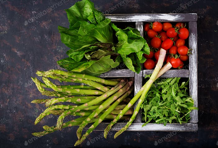 Fresh asparagus, tomato. arugula and lettuce in wooden box  on dark background