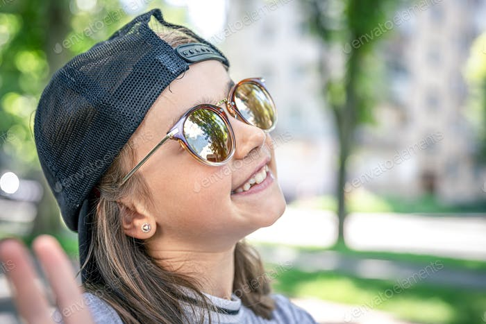 Portrait of a stylish little girl in sunglasses outdoors.