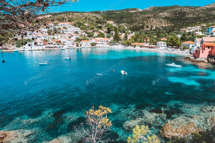 View on tourquise transparent bay of mediterranean village Assos framed through green pine grove