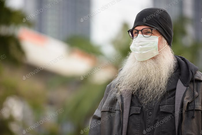 Face of mature bearded hipster man with mask thinking outdoors