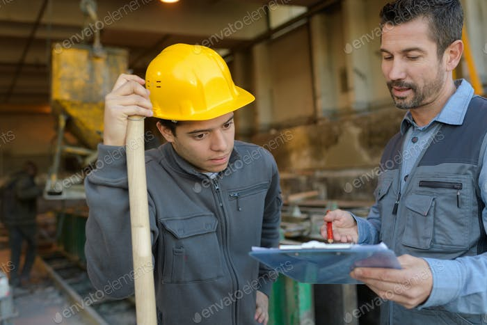 engineer discussing over clipboard at construction site