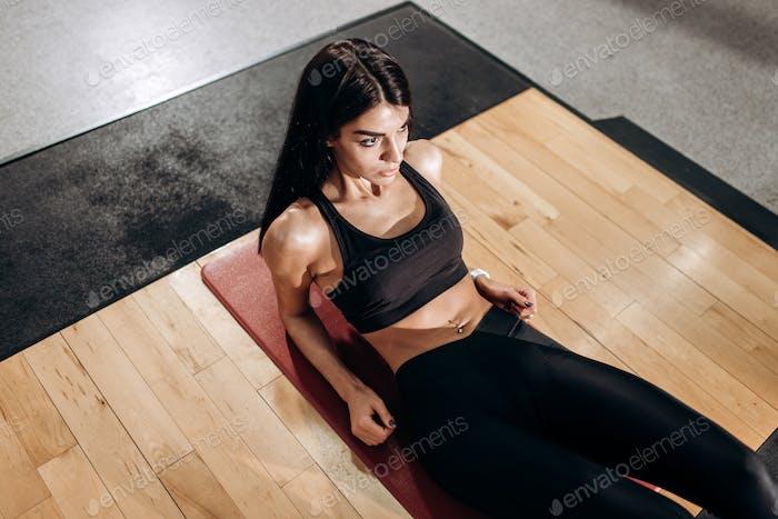 Schlankes Mädchen in schwarzem Sporttop und Strumpfhosen macht Übungen für die Bauchmuskeln auf dem