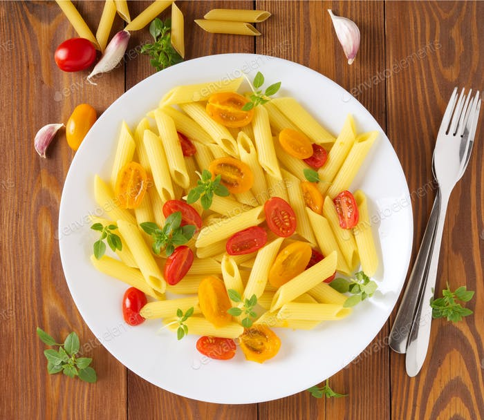 Penne pasta with yellow and red tomatoes decorated with basil on brown wooden background