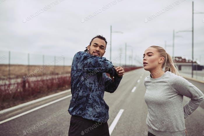 Пара в спортивной одежде растягивается перед бегом на загородной дороге