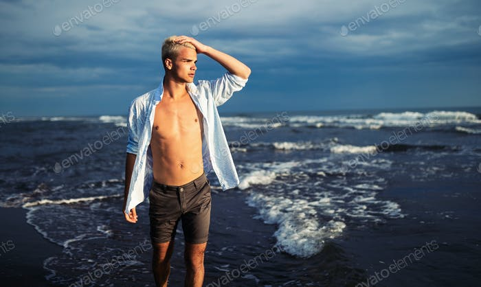 Handsome man standing at sea beach while on vacation