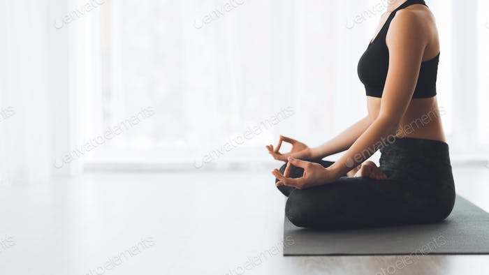 Keep calm. Woman sitting in lotus position on floor