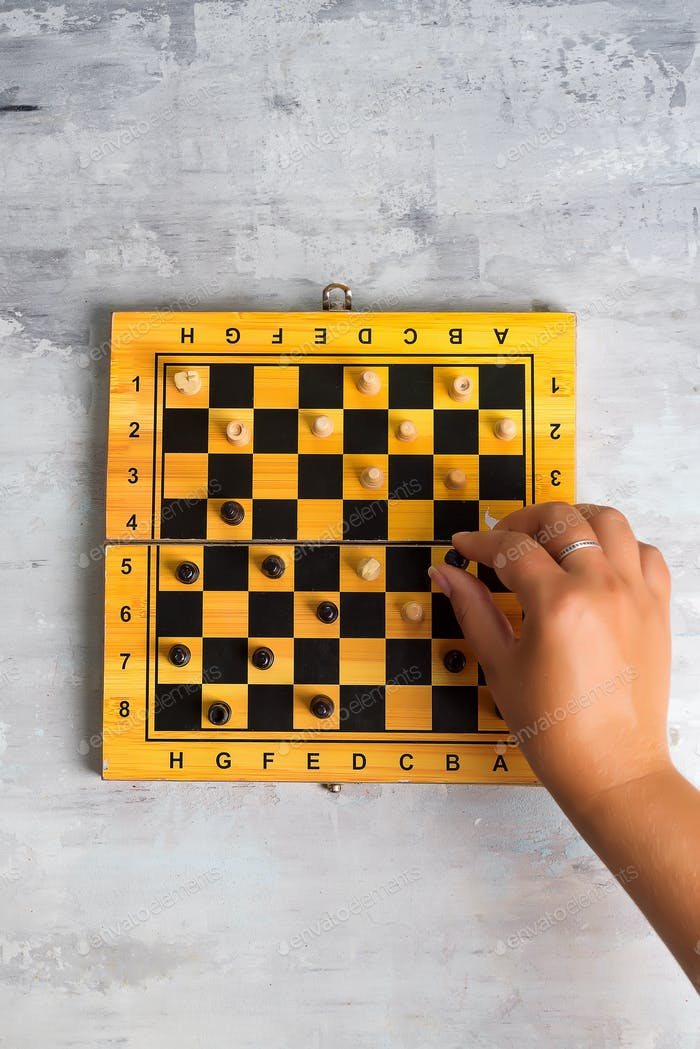 wooden chess board and woman's hand making chess move