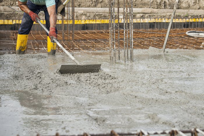 a bricklayers who level the freshly poured concrete to lay the foundations of a building