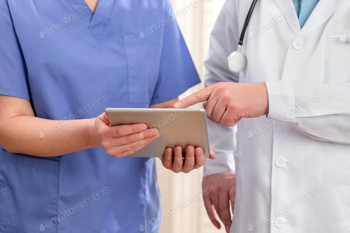 Doctor and nurse discussing patients tests at tablet computer in hospital