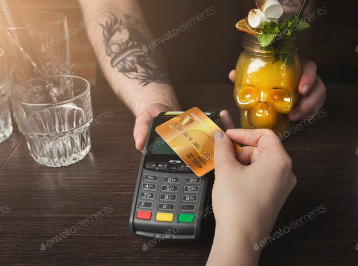 Woman paying for cocktail with credit card at bar counter