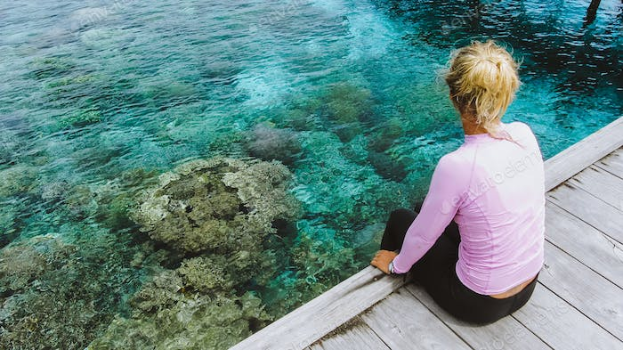 Girl sitting on a wooden jetty near Mansuar island in Raja Ampat. Beautiful colorful corals visible