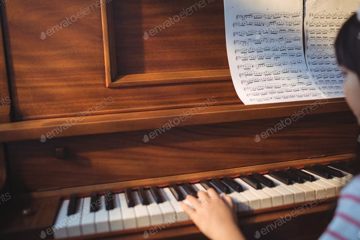 Cropped image of girl practicing piano
