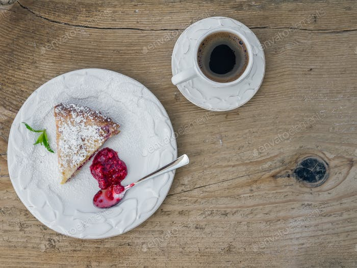 A piece of raspberry cheesecake and a cup of coffee on a wooden