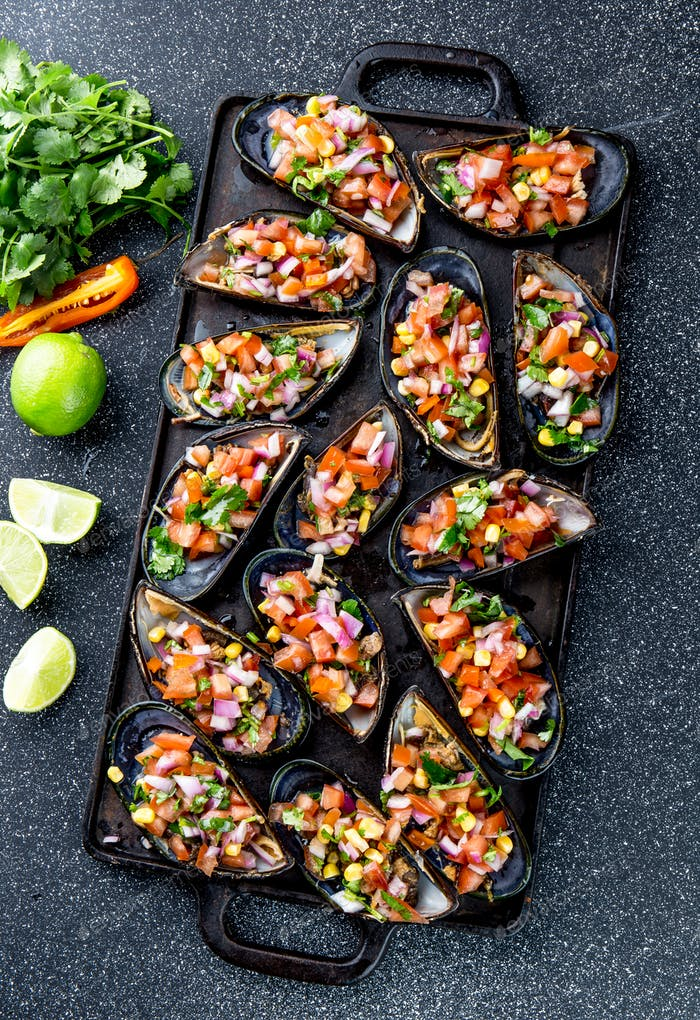 Big mussels, choros zapatos seasoned with purple onion, tomatoes, corn and lemon