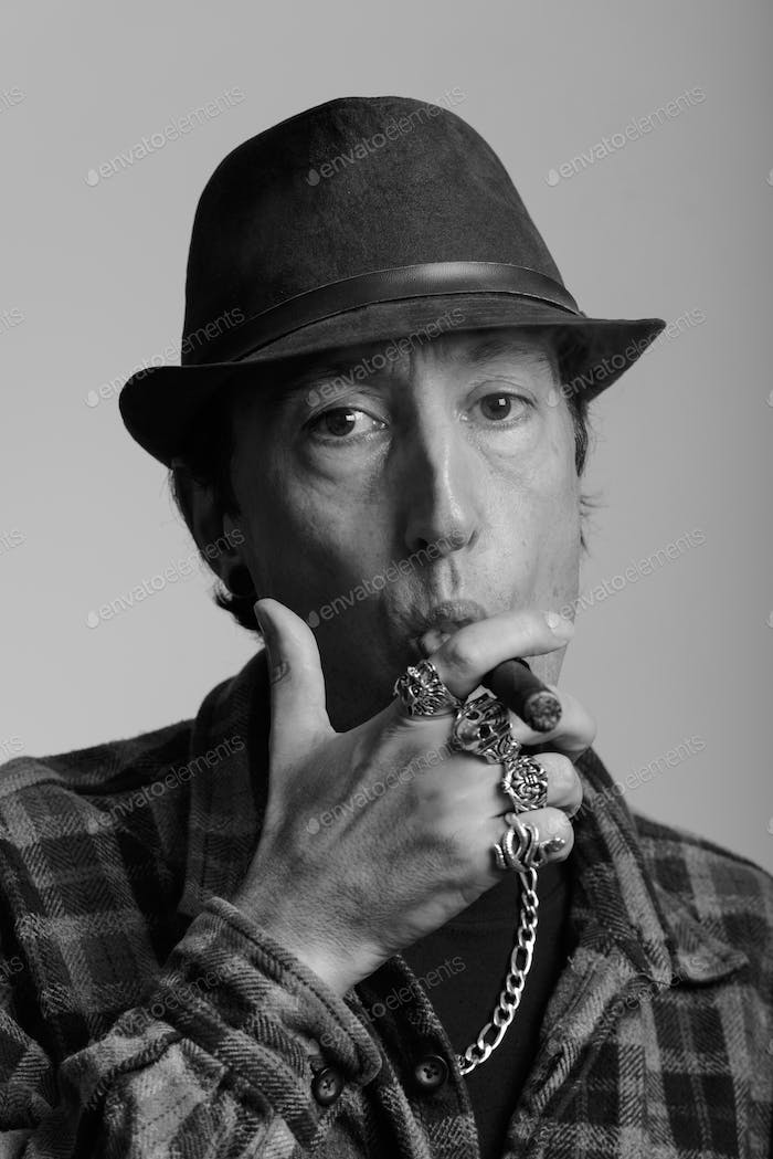 Face of mature gangster man smoking cigar in black and white