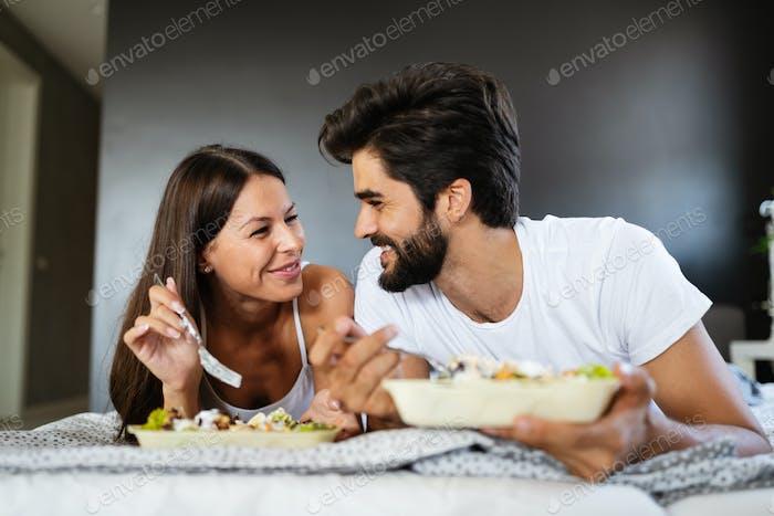 Glückliches Paar in der Liebe mit Frühstück im Bett
